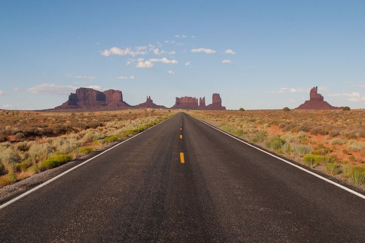 Scenic view of empty road leading to rock formations