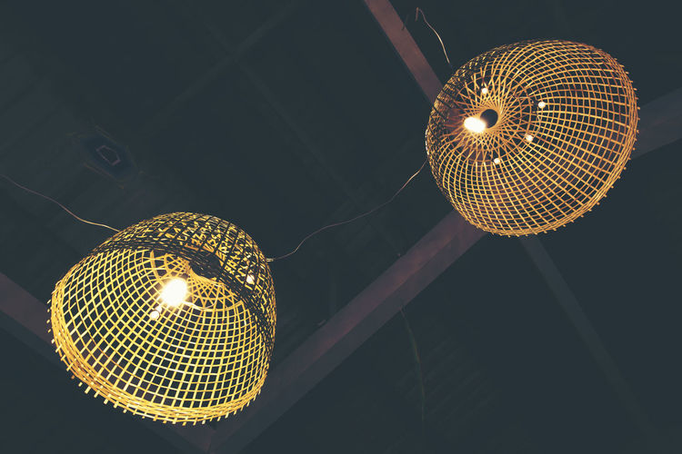 Low angle view of illuminated lighting equipment hanging on ceiling