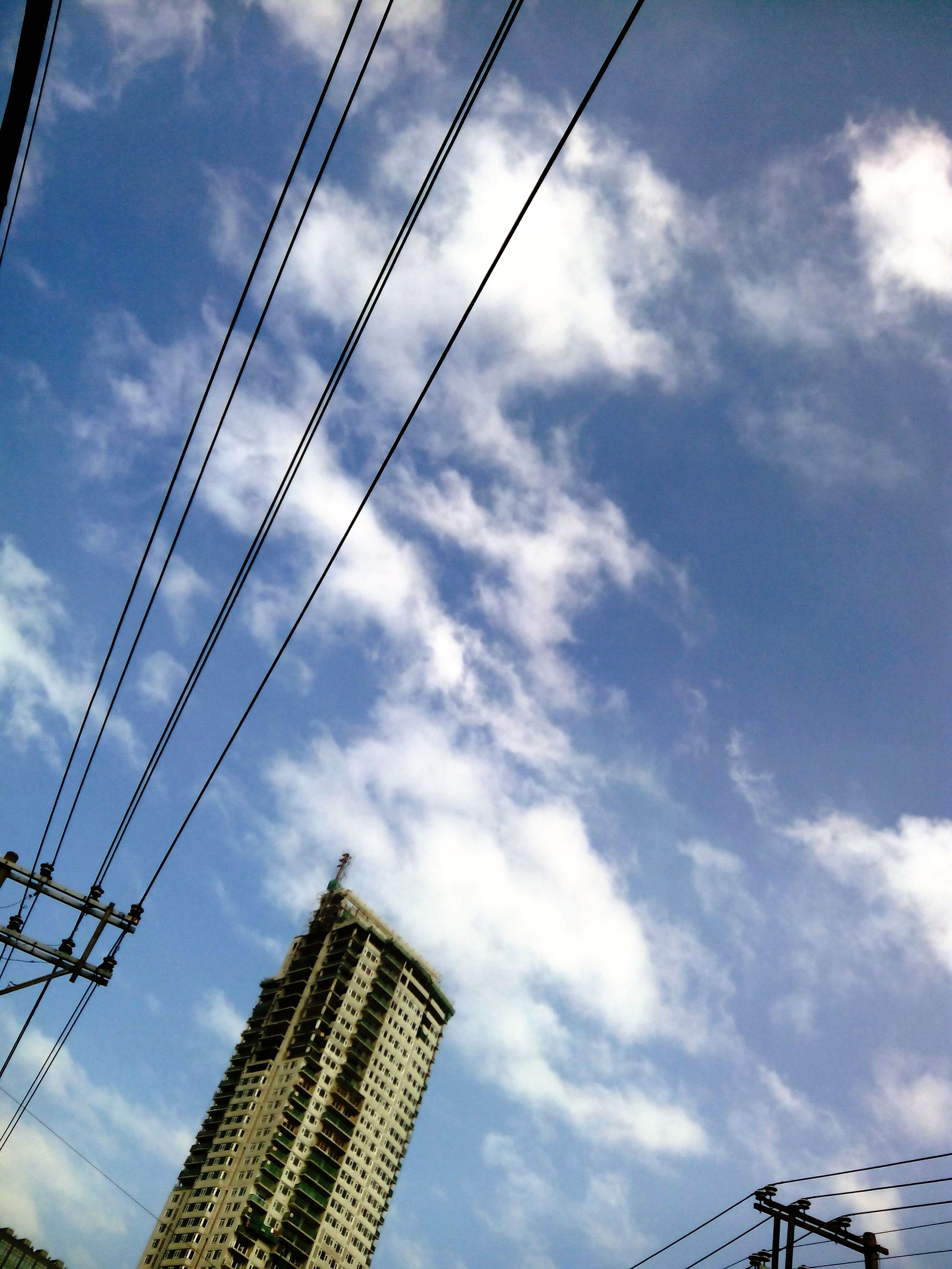 low angle view, power line, sky, cable, electricity pylon, electricity, connection, built structure, architecture, power supply, cloud - sky, building exterior, fuel and power generation, technology, cloudy, cloud, tall - high, outdoors, no people, silhouette