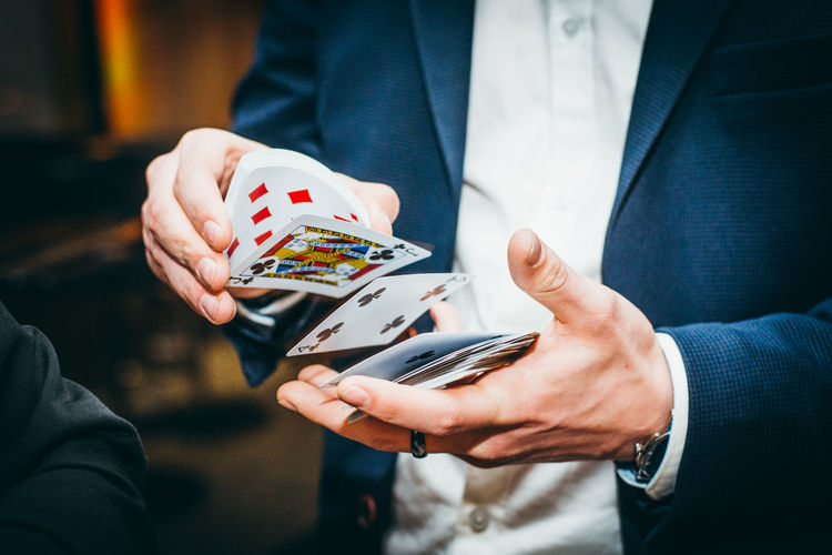 Midsection of man gambling playing cards in casino