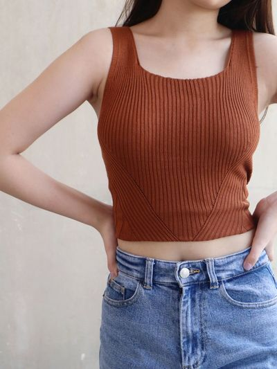 Midsection of woman standing against wall