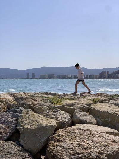 Full length of boy standing on rock against sky