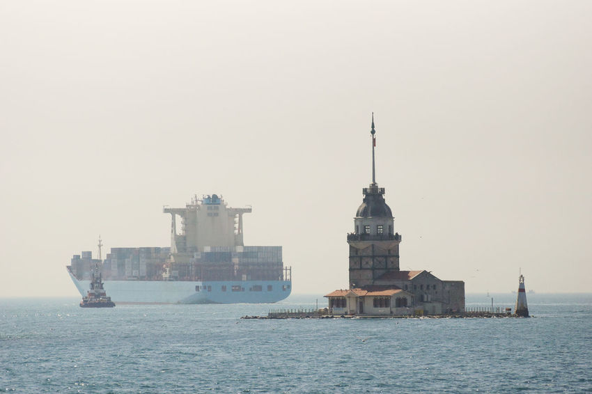 Maiden's Tower with a Container Vessel passing the Bosporus on a hazy Spring Day in the Background Bosporus Cargo Ship Container Vessel Containership Day Fog Global Trade Haze Historical Building Industry Istanbul Landmark Maiden's Tower Marmarasea Nautical Vessel No People Outdoors Sailing Sea Ship Shipping  Trade Tug Turkey Water