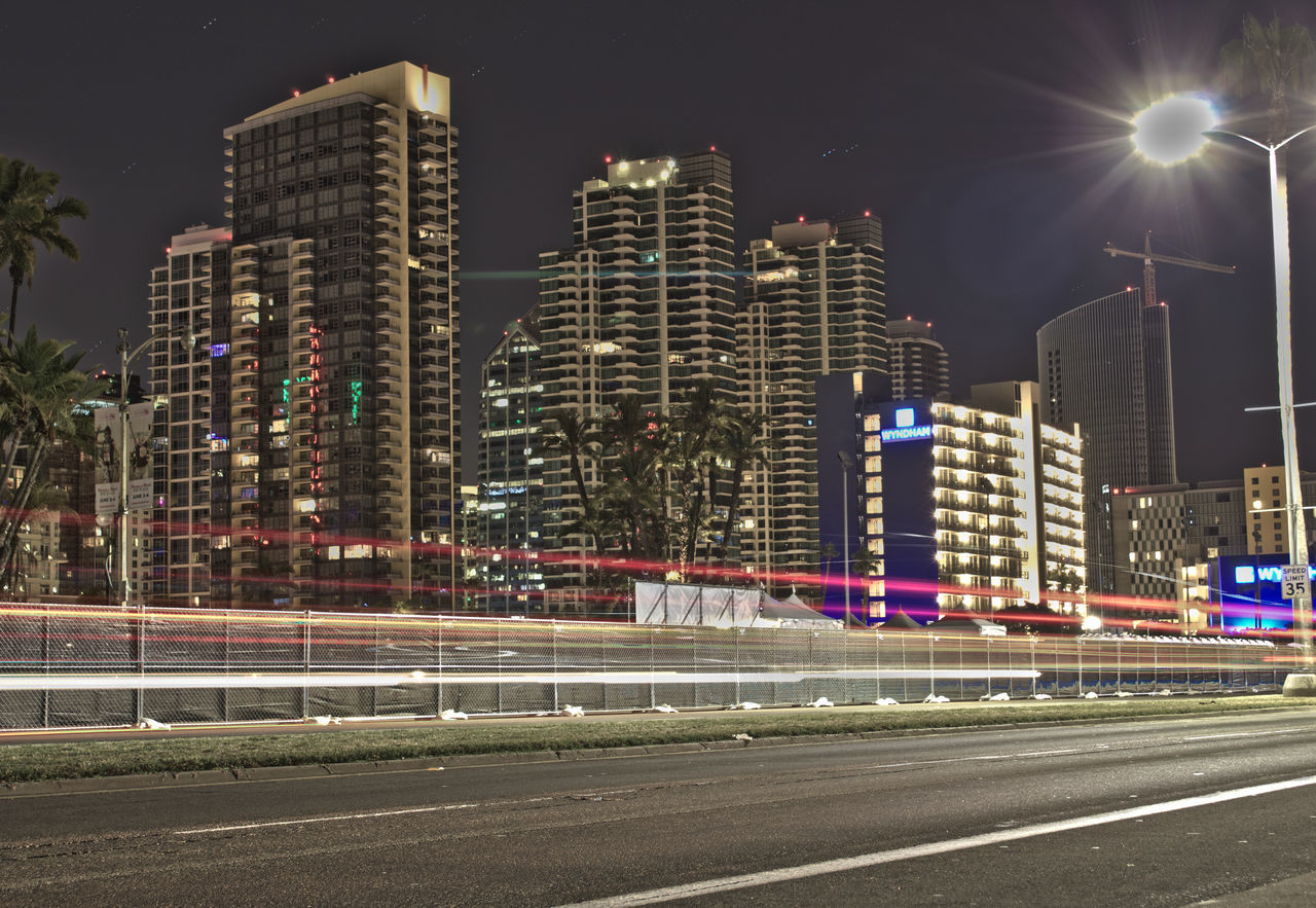 illuminated, night, architecture, building exterior, built structure, city, light trail, modern, long exposure, skyscraper, motion, speed, road, urban scene, no people, outdoors, travel destinations, cityscape, high street, sky