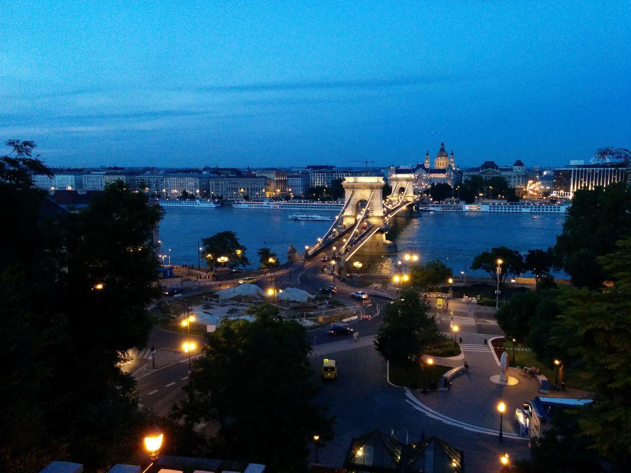 Illuminated Bridge Over River Against Blue Sky At Dusk