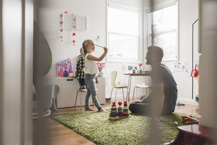 Father playing with daughter seen through window at home