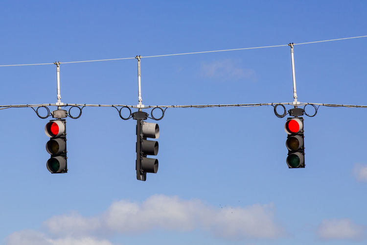 Low angle view of road signals against sky