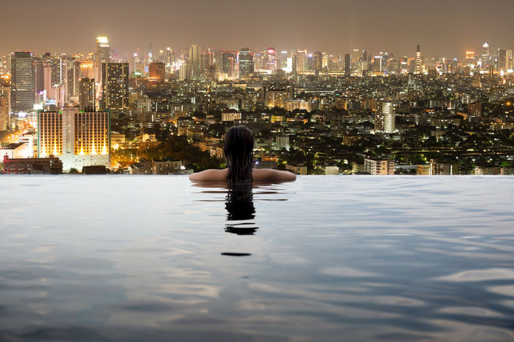 Young Asian woman in swimming pool look over city at night Architecture Building Exterior Built Structure City Cityscape Illuminated Modern Night One Person Outdoors People Real People Reflection Sky Skyscraper Urban Skyline Water Waterfront