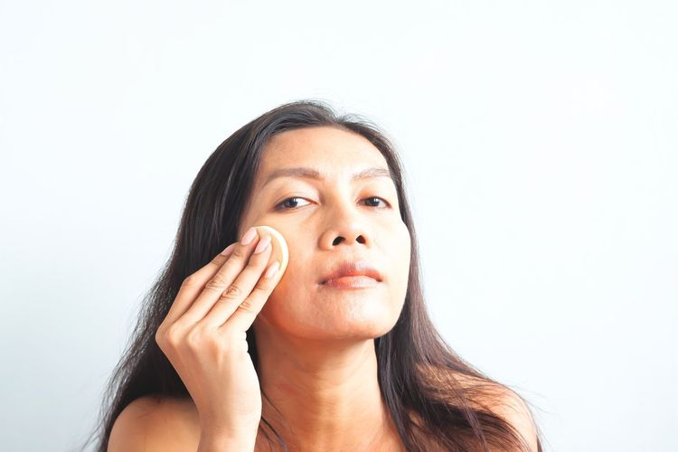Asian woman looking at camera and applying foundation powder on her face. Beauty concept Problem Zits Pimples Acne Powder Asian  ASIA Diversity Skin Imperfection Contemplation Human Face Hand Hairstyle Body Part Beautiful Woman Human Body Part Cut Out Looking At Camera Young Women Beauty Adult Hair Front View Young Adult Indoors  Women White Background Copy Space One Person Studio Shot Portrait Headshot