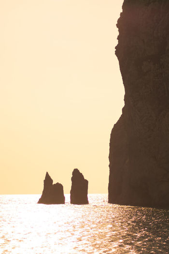 Silhouette rock formations by sea against clear sky