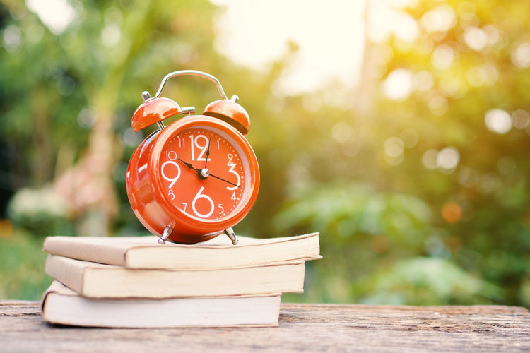 Orange alarm clock and book on table outdoors