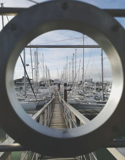 Boats moored at harbor seen through hole