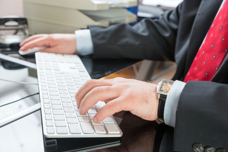 Cropped Image Of Businessman Using Computer At Desk In Office