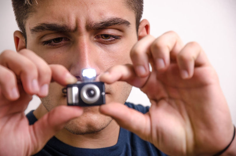 Close-up portrait of young man holding camera