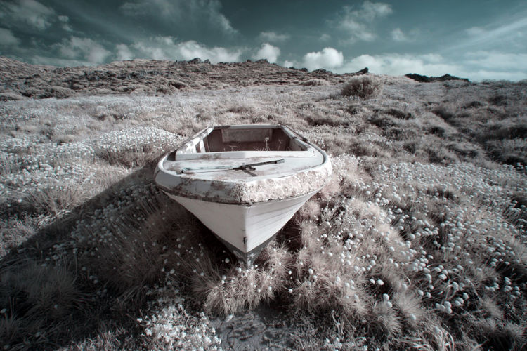 Abandoned boat on land against sky