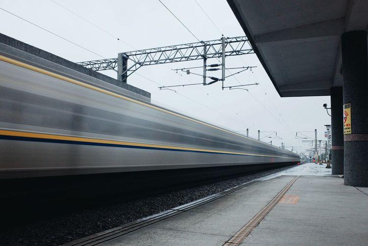 Train speeding by railroad station platform against sky