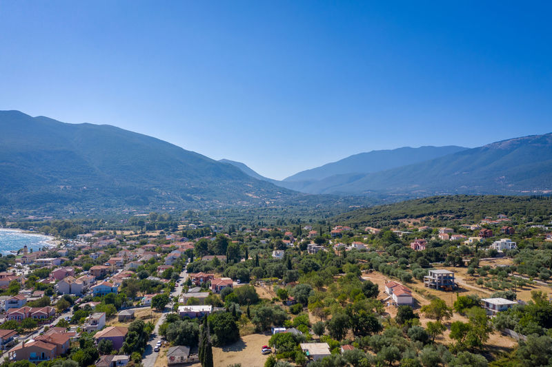 Aerial view of townscape and mountains against clear blue sky