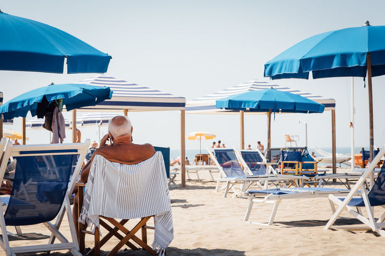 Rear view of senior man sitting on chair at beach