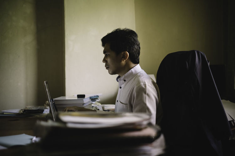 Side view of businessman working at desk in office