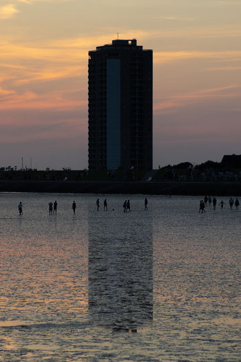 Sea by buildings against sky during sunset