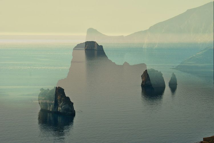 Scenic view of sea against sky, rocky coastline double exposure