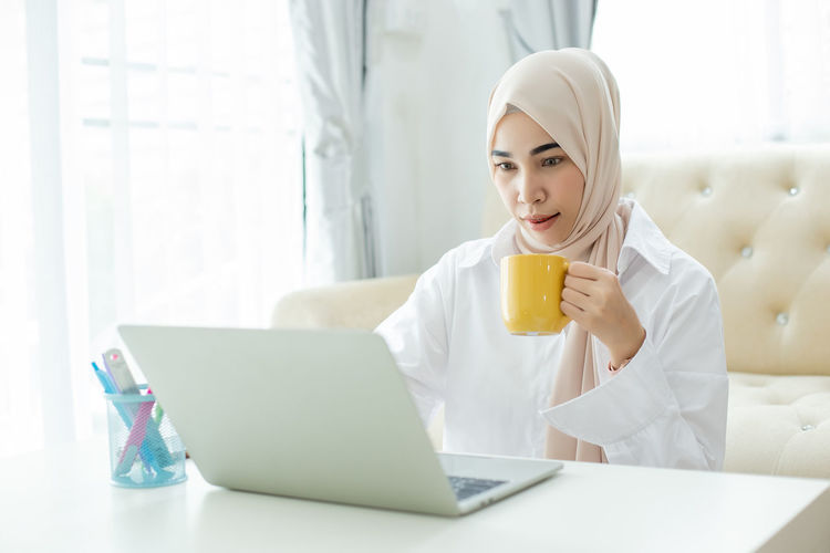 Young woman using mobile phone in laptop