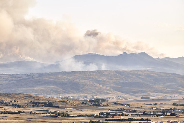 Photograph of a large forest fire with a large column of smoke on a hillside near a city
