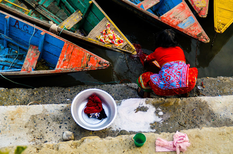 High Angle View Of Woman Washing Clothes In Water