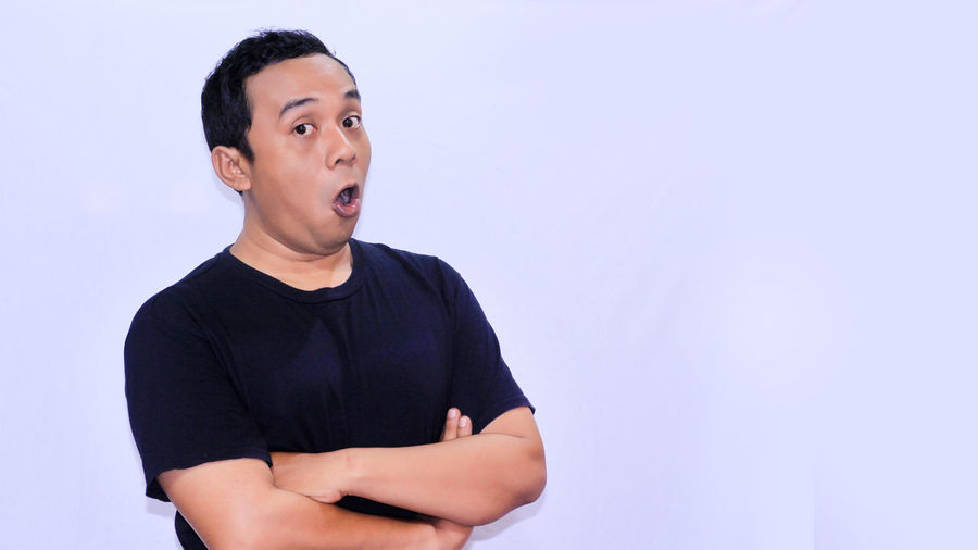 Portrait of a young funny Asian man shocked or surprised expression with mouth open Front View One Person Young Adult Casual Clothing Young Men Looking Copy Space Studio Shot Lifestyles Waist Up Indoors  Looking Away Wall - Building Feature Standing Portrait Black Color T-shirt Mouth Open Contemplation Spiky Hair