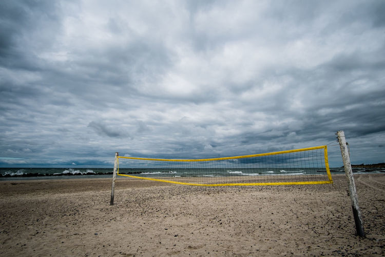 Volleyball net at beach against cloudy sky