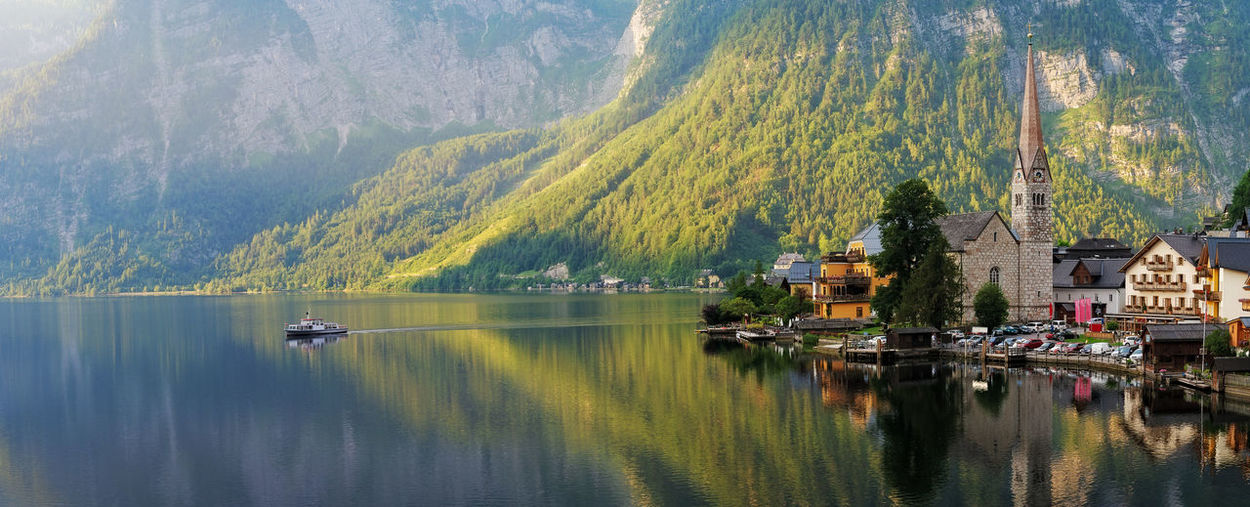 Panoramic view of lake by buildings and mountains
