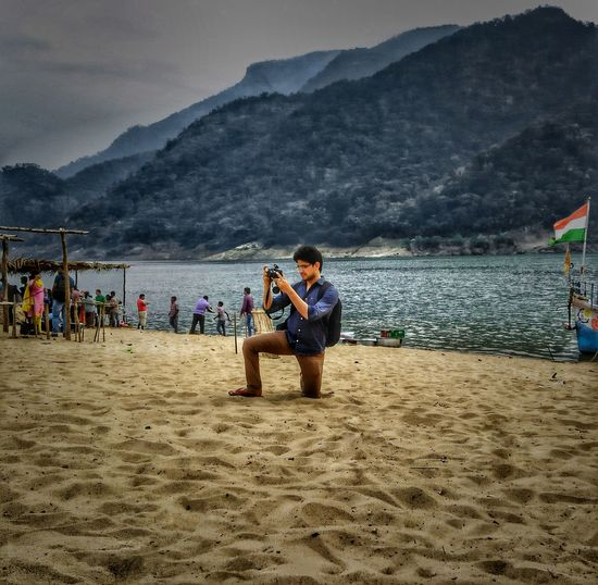Full length of man photographing at beach