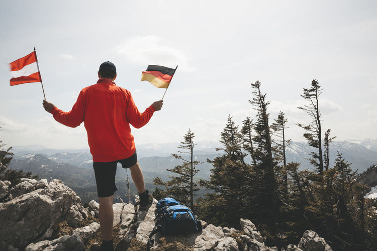 Rear view of mature man holding national flags while standing on mountain against sky