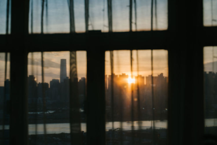 Silhouette buildings against sky during sunset seen through glass window