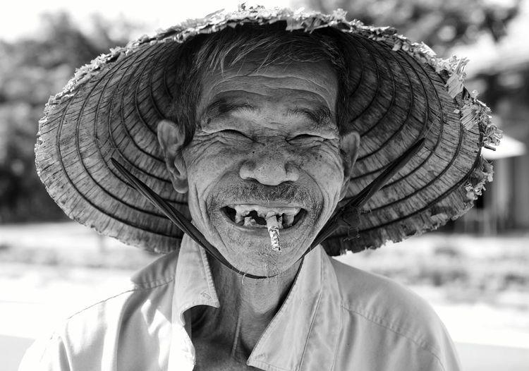 Portrait of smiling man smoking cigarette