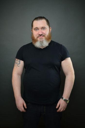 Portrait of man standing against black background
