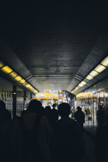 Rear view of people walking on illuminated railroad station platform
