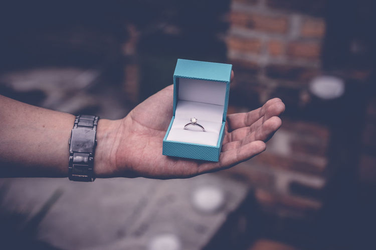 Cropped Hand Of Man Holding Engagement Ring Box