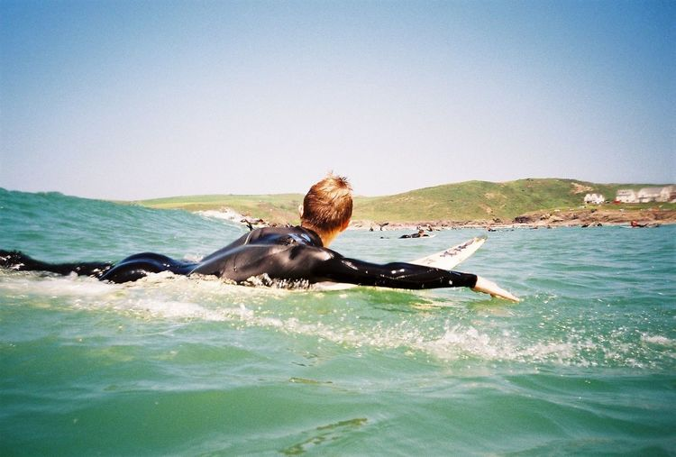 Side view of man surfboarding in sea against sky