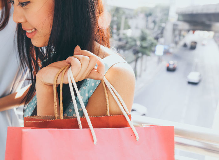 Close-up of woman holding shopping bag in store