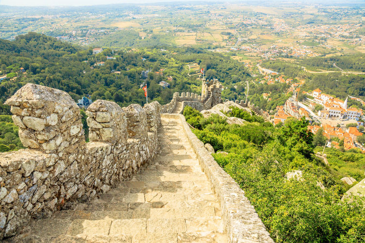 Aerial view of ancient wall and tower of Castle of the Moors and Sintra valley. Castelo dos Mouros is medieval castle and Unesco Heritage on a hill above Sintra, Lisbon District, Portugal. Pena Palace and the ruins of Moors Castle are popular landmarks and major tourist attractions of the Cultural Landscape of Sintra as a World Heritage Site, Portugal. Portugal Sintra Castle Ruins Medioeval Cities Wall Tourism Flags Skyline Cityscape Palace Castle Ruin Aerial View Moors Castle Pena Palace Moors Architecture History The Past Built Structure Ancient Travel Destinations Tree Ancient Civilization Plant Nature Scenics - Nature Landscape Stone Material No People Old Ruin Solid Old Building Exterior Environment Archaeology Outdoors Stone Wall