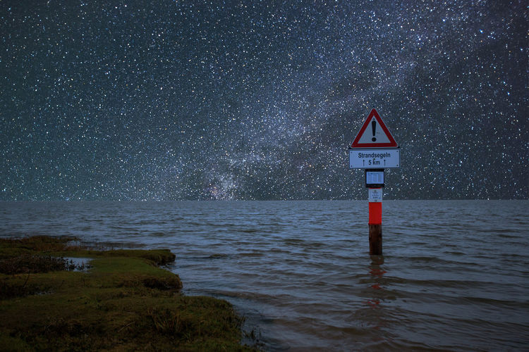 Sign Communication Warning Sign Water Guidance Sky No People Night Scenics - Nature Nature Tranquility Tranquil Scene Road Sign Beauty In Nature Land Outdoors Information Safety Triangle Shape Stars Milky Way Germany Urlaub Holiday Nordsee