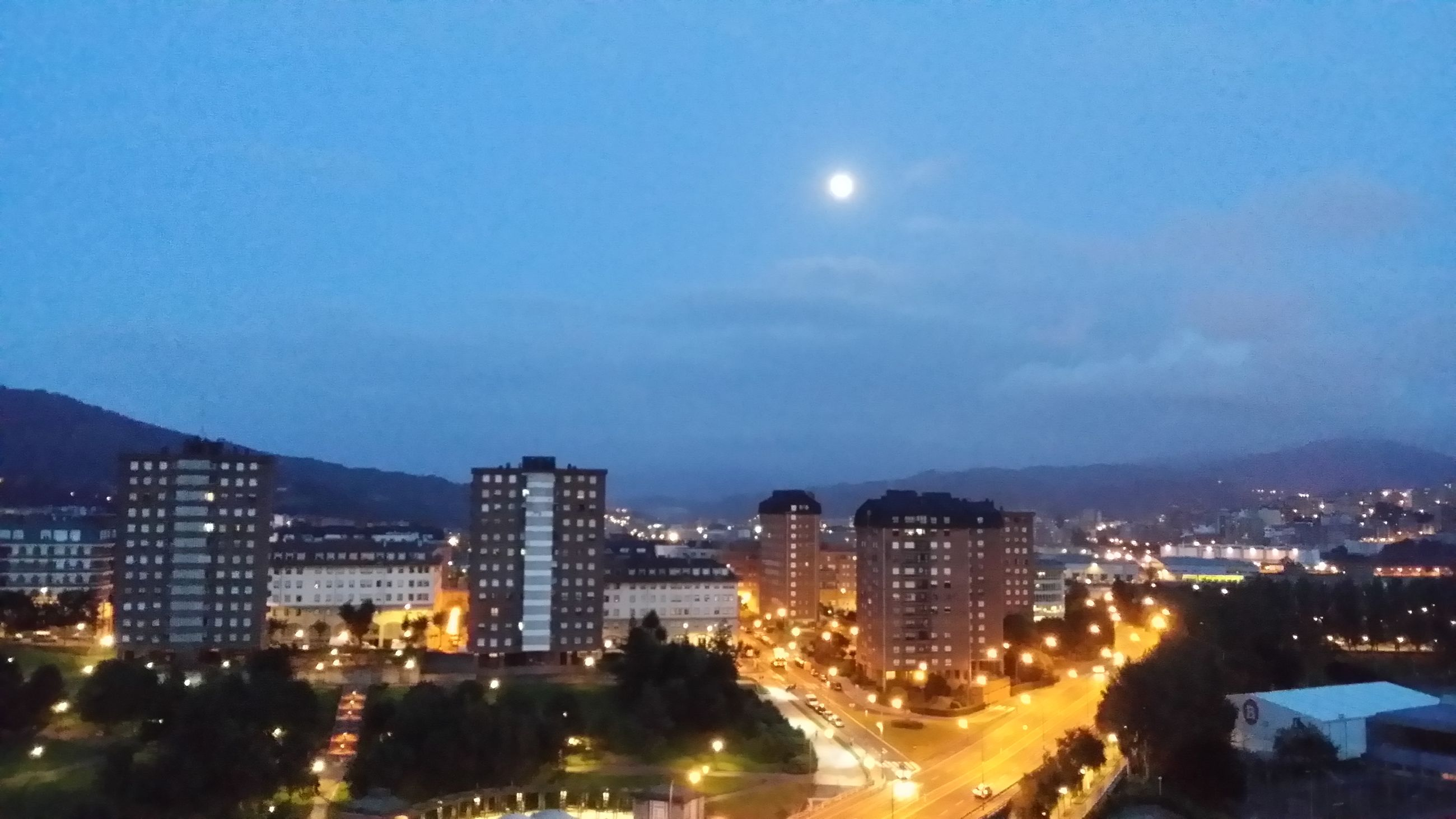 illuminated, night, building exterior, city, cityscape, architecture, built structure, sky, moon, high angle view, residential district, residential building, mountain, city life, residential structure, dusk, outdoors, crowded, light - natural phenomenon, no people