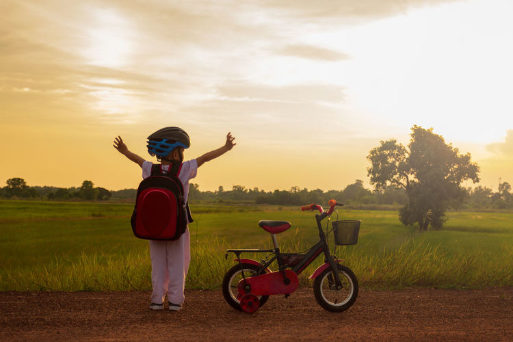 Rear view of boy standing by bicycle on dirt road during sunset