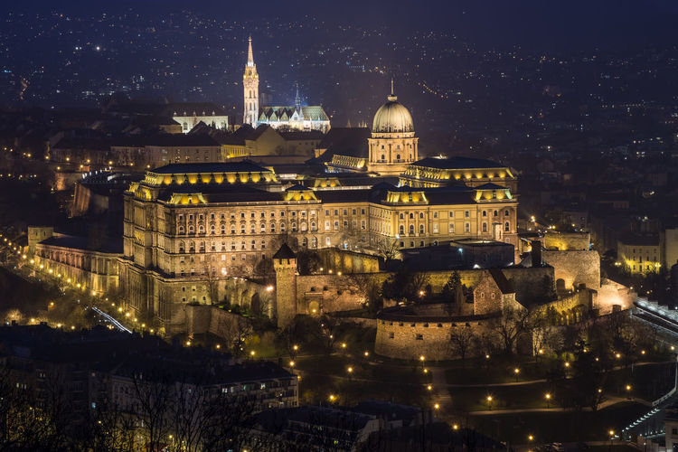 Illuminated royal palace of buda in city at night