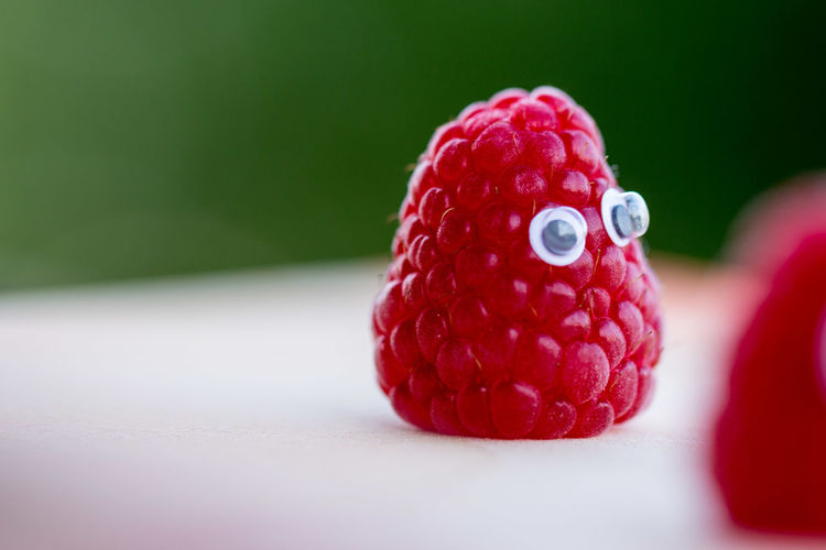 Close-up of raspberry with googly eyes on table