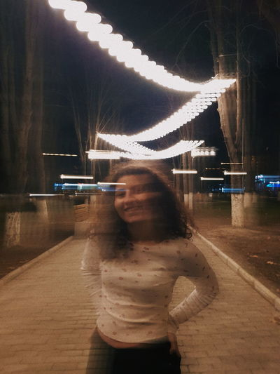 Digital composite image of woman standing at night