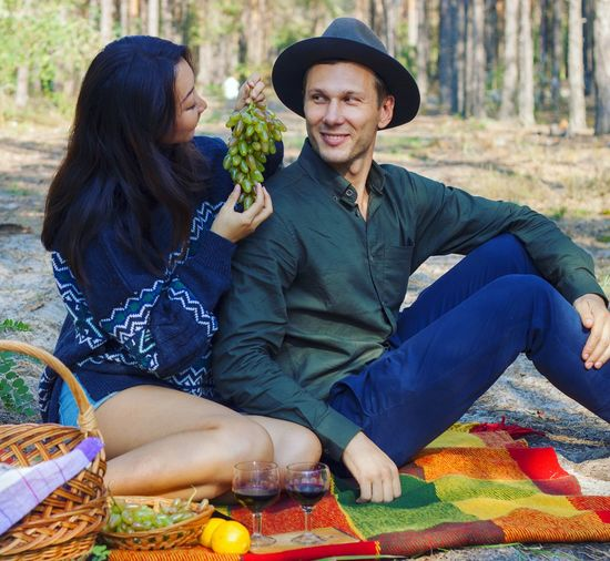 Woman feeding grapes to boyfriend while having picnic in forest