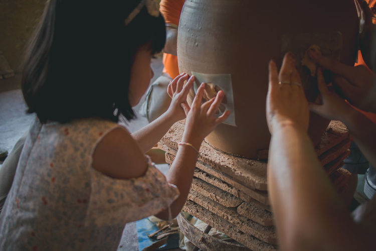 Side view of girl making floral pattern on pottery in workshop