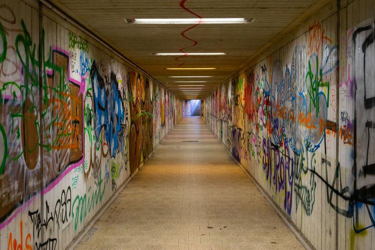 Graffiti on wall of illuminated tunnel